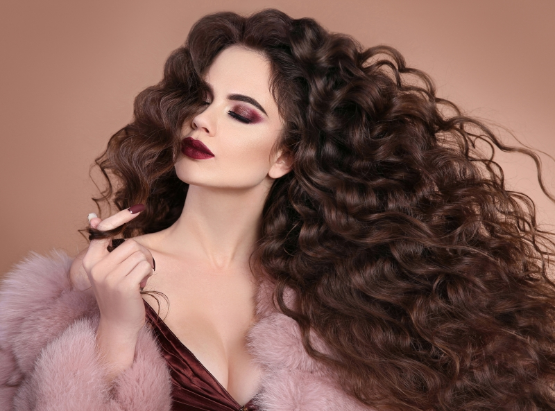 Hairstyle. Fashion brunette girl with Long curly hair, beauty makeup. Glamour portrait of beautiful brunette with marsala matte lips in pink fur coat isolated on beige background.